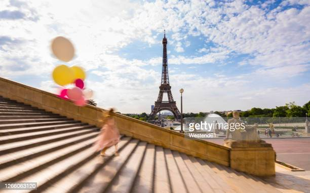 woman with balloons climbing down staircase against eiffel tower in paris, france - paris france stock pictures, royalty-free photos & images