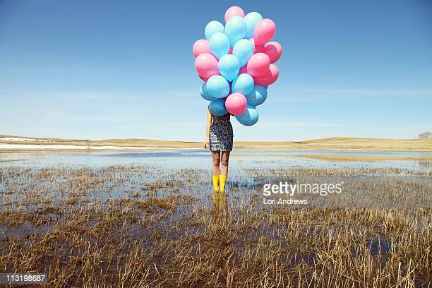 woman with balloons in spring field - gummistiefel frau stock-fotos und bilder