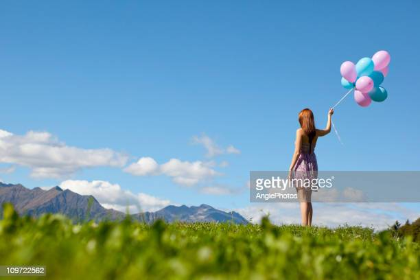 Frau mit Ballons looking at view