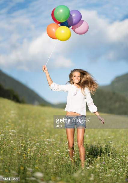 woman with balloons running through the meadow - hot pants stock pictures, royalty-free photos & images