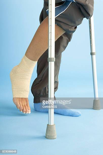 woman with bandaged ankle on crutches - elastic bandage stock photos and pictures