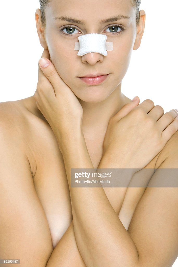 Woman with bandaged nose, arms folded across chest, looking at camera : Stock Photo