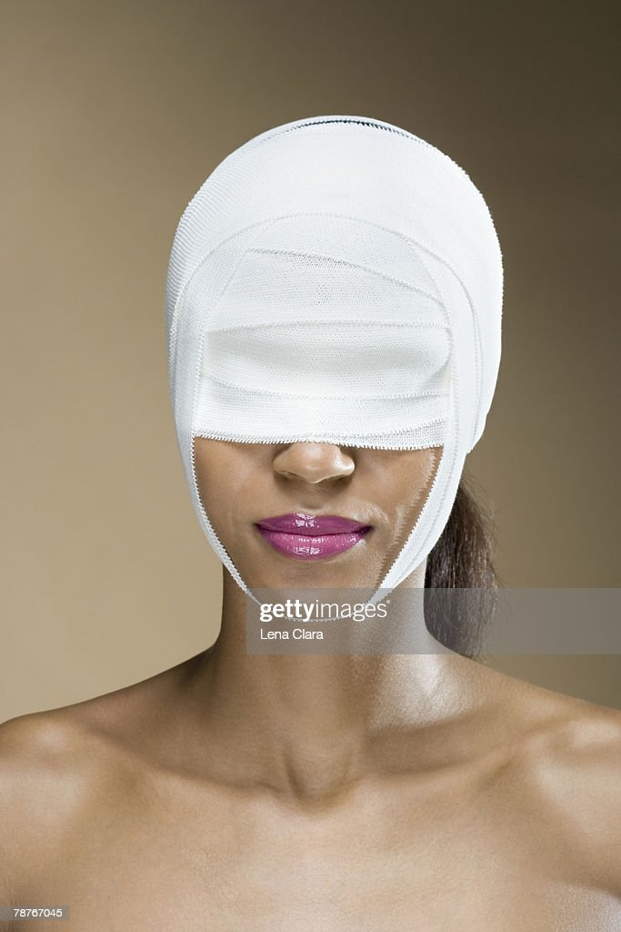 A woman with bandages wrapped around her face : Stock Photo