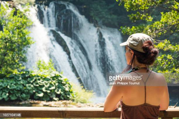 woman with bare shoulders watching the watching the waterfalls in martin brod, una national park, bosnia and herzegovina - national landmark stock pictures, royalty-free photos & images