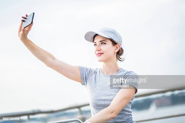 Woman with basecap taking selfie with cell phone