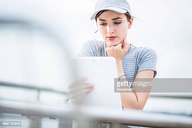Woman with basecap using tablet