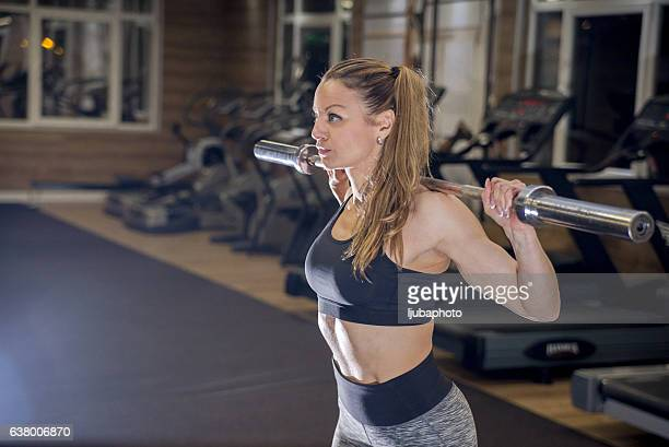 woman with beautiful athletic body doing exercises with barbell