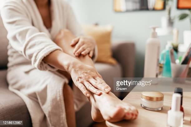 femme avec le masque de visage de beauté massant ses jambes et ses pieds - beaux pieds et femme photos et images de collection