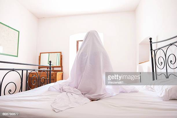 Woman with bed sheet sitting on bed
