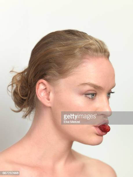 woman with berry in her mouth