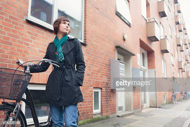 Woman with bicycle in residential district of Copenhagen, Denmark.