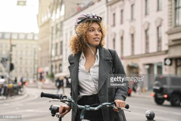 woman with bicycle in the city, berlin, germany - monter un animal ou sur un moyen de transport photos et images de collection