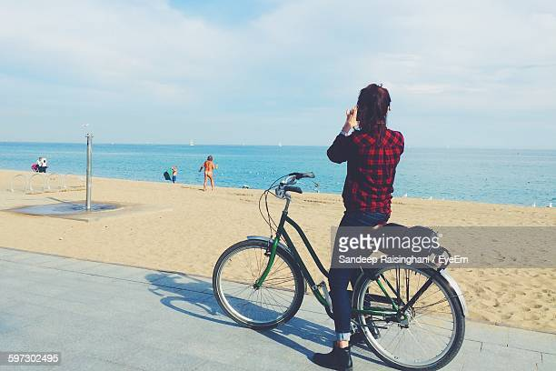 Woman With Bicycle On Promenade By Beach Looking At Horizon