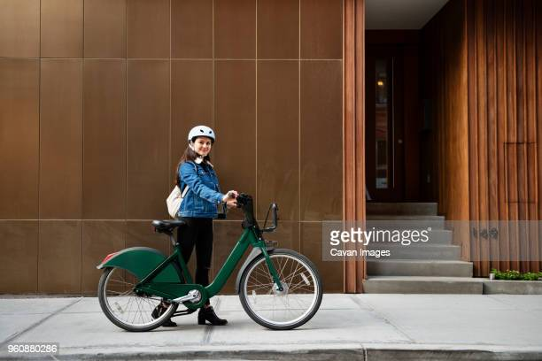 Woman with bicycle on sidewalk by building