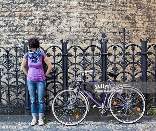 woman with bicycle on sidewalk with wrought iron fence - purple shirt stock photos and pictures