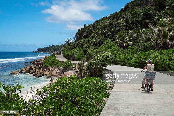 woman with bicycle on tropical coast road - la digue island stock pictures, royalty-free photos & images