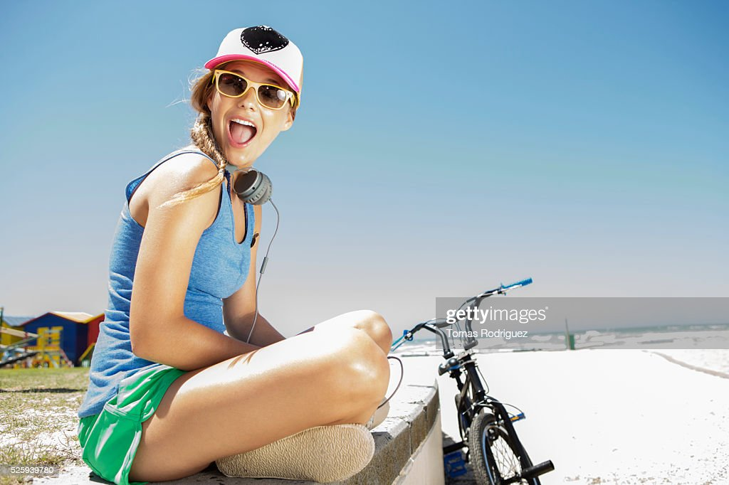 Woman with bicycle sitting on beach : Foto de stock