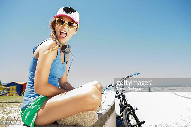 Woman with bicycle sitting on beach