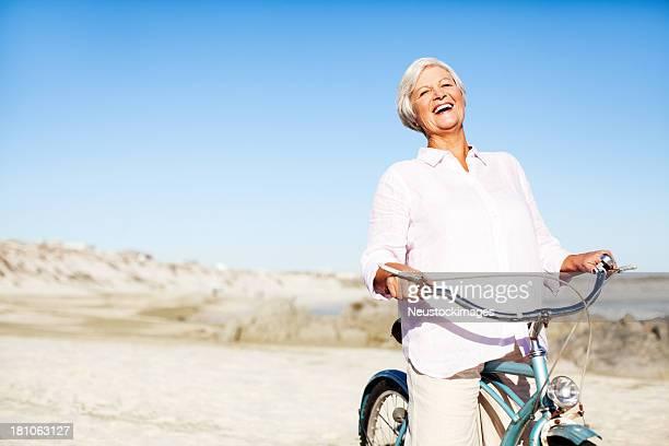 Femme avec vélo contre le ciel bleu transparent sur la plage