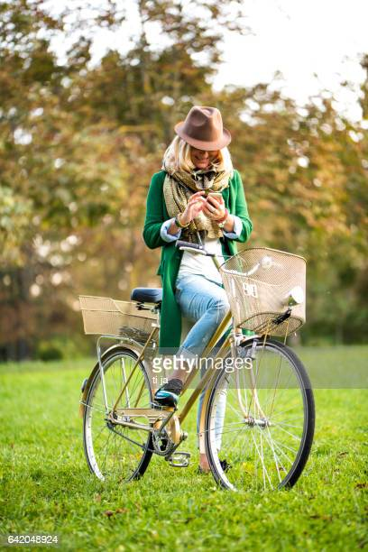 Woman with bicycle using a smart phone in nature