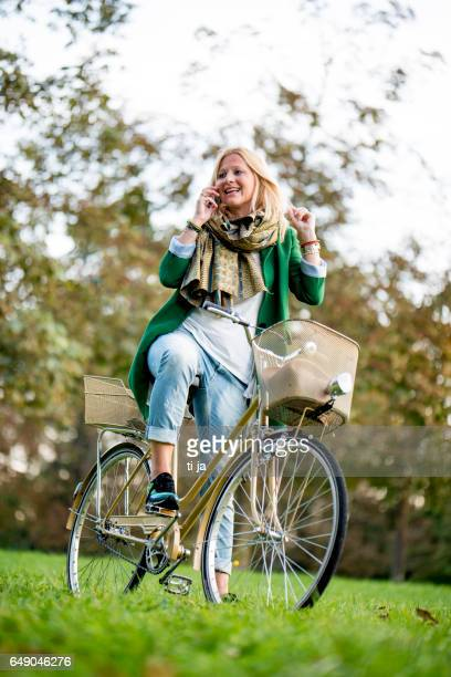 woman with bicycle using a smart phone in nature - gold pants stock photos and pictures