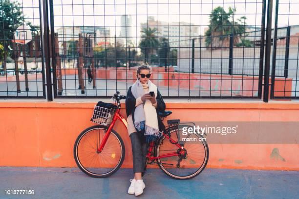 femme à vélo à l'aide de téléphone en espagne - une seule jeune femme photos et images de collection