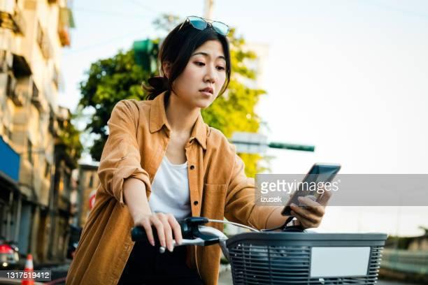 woman with bicycle using smart phone in city - izusek imagens e fotografias de stock