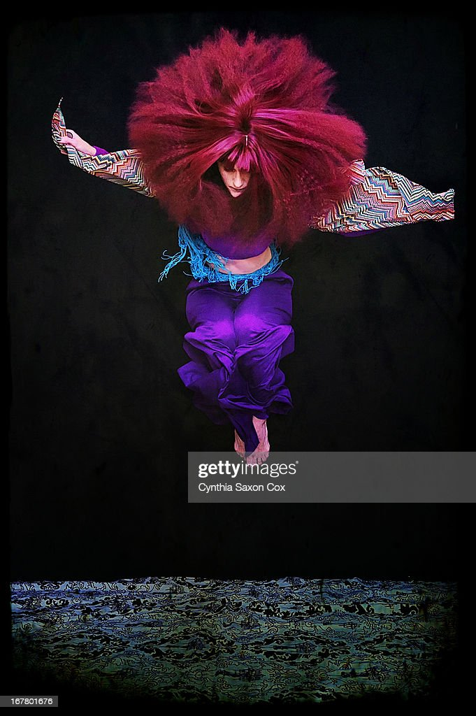 Woman with big hair jumping : Stock Photo