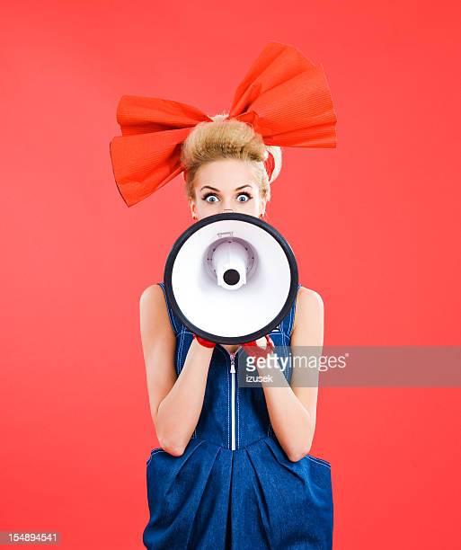 Woman with big hair ribbon shouting into megaphone