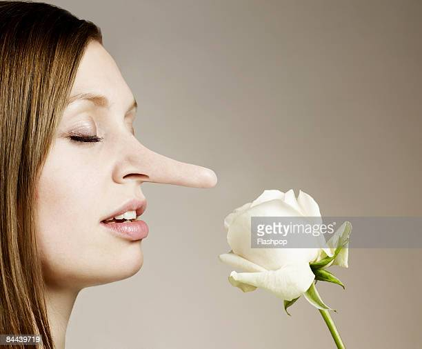 woman with big nose smelling flower - nariz humano imagens e fotografias de stock