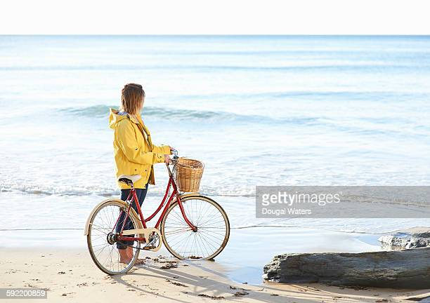 Woman with bike and yellow rain coat at beach.