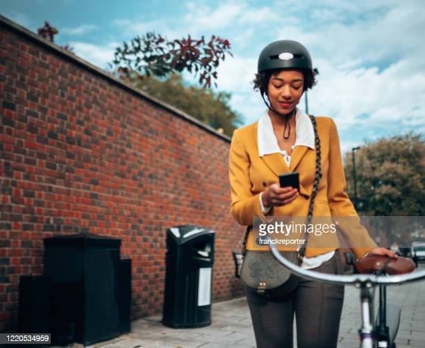 woman with bike commuting in london - bicycle stock pictures, royalty-free photos & images