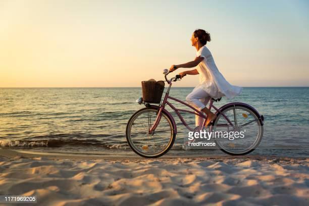 夕暮しの時にビーチで自転車を持つ女性 - ウセドム ストックフォトと画像