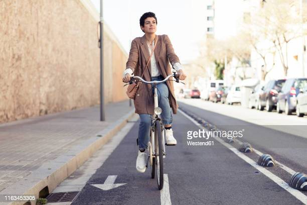 woman with bike on bicycle lane in the city - montar imagens e fotografias de stock
