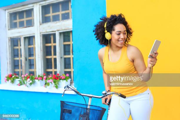 woman with bike using smart phone - multi colored background stock pictures, royalty-free photos & images