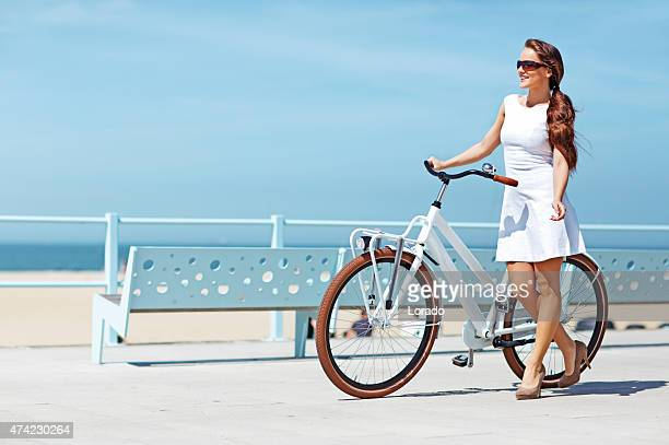 woman with bike walking near the sea