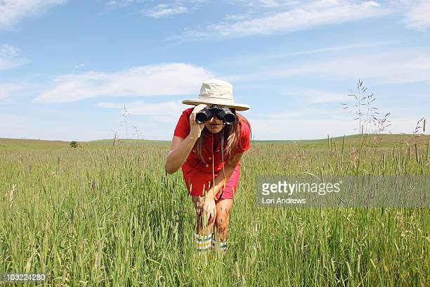Woman with binoculars in field