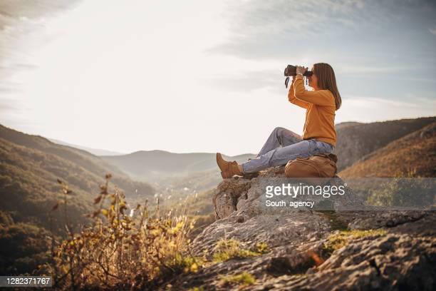 woman with binoculars sitting on mountain peak in sunset - binoculars stock pictures, royalty-free photos & images