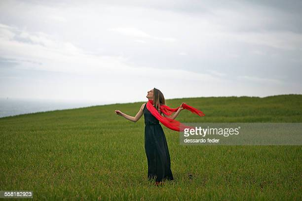 woman with black dress and red pashmina on the gre - black dress stock pictures, royalty-free photos & images