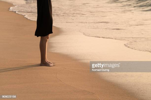 woman with black dress standing lonely on the beach. - 黒のドレス ストックフォトと画像
