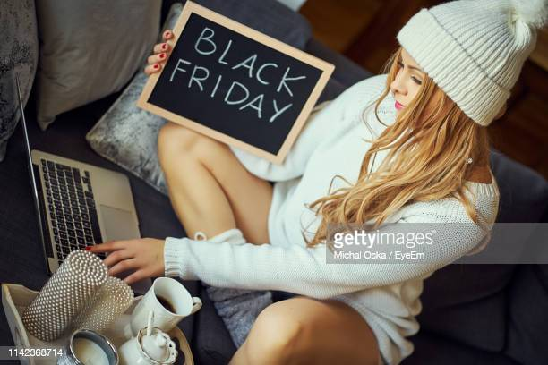 woman with black friday text sitting on sofa at home - black friday stock photos and pictures