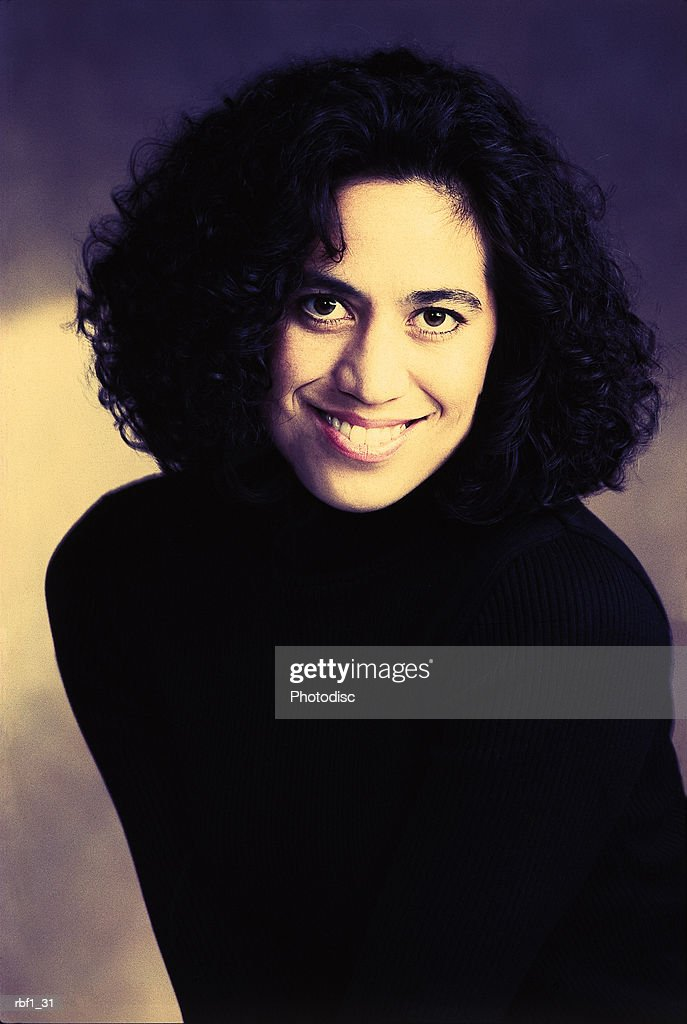 woman with black hair wearing a black turtleneck smiles at the camera : Stockfoto