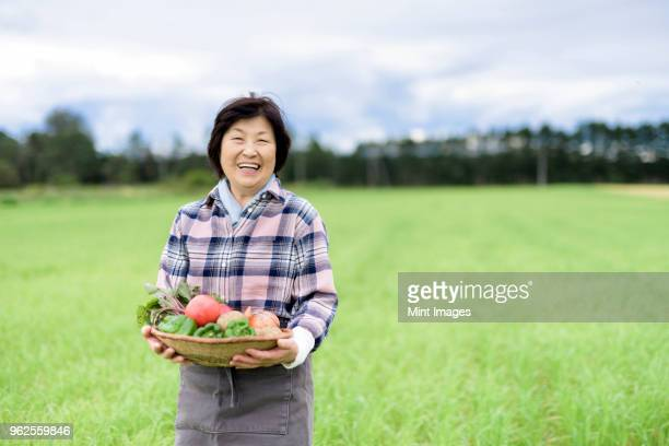 woman with black hair wearing checkered shirt standing in a field, holding basket with fresh vegetables, smiling at camera. - 農業 ストックフォトと画像