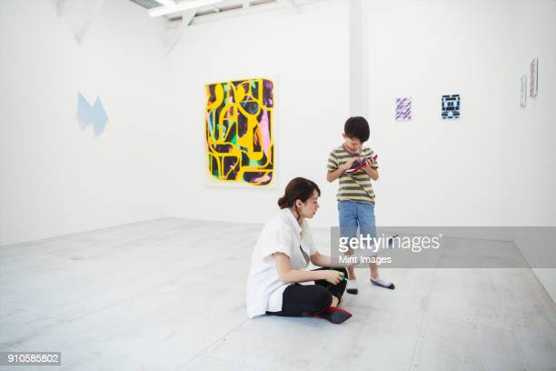 Woman with black hair wearing white shirt sitting on floor in art gallery with pen and paper, boy standing beside her.