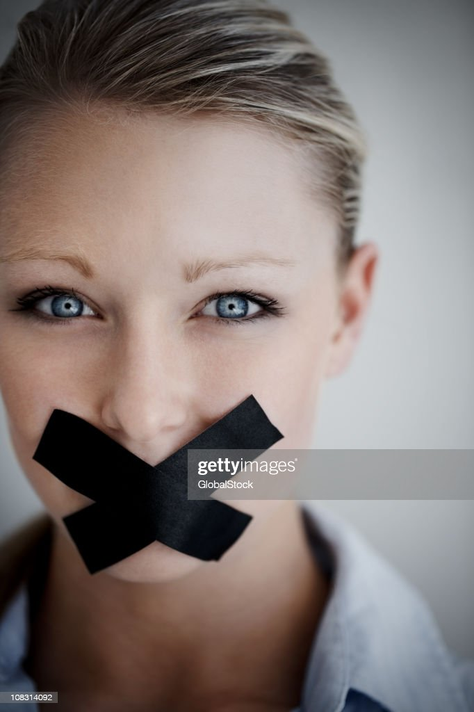 Woman with black tape on mouth representing no speech : Stock Photo