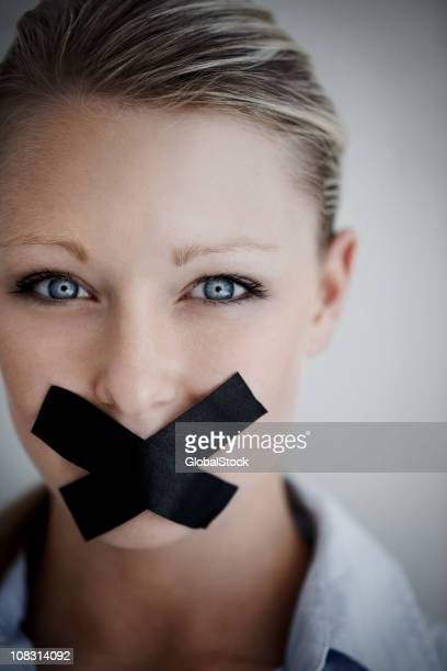Woman with black tape on mouth representing no speech