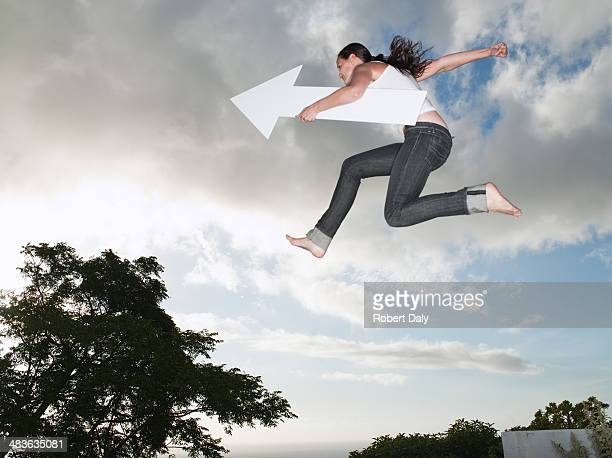 Woman with blank arrow leaping outdoors