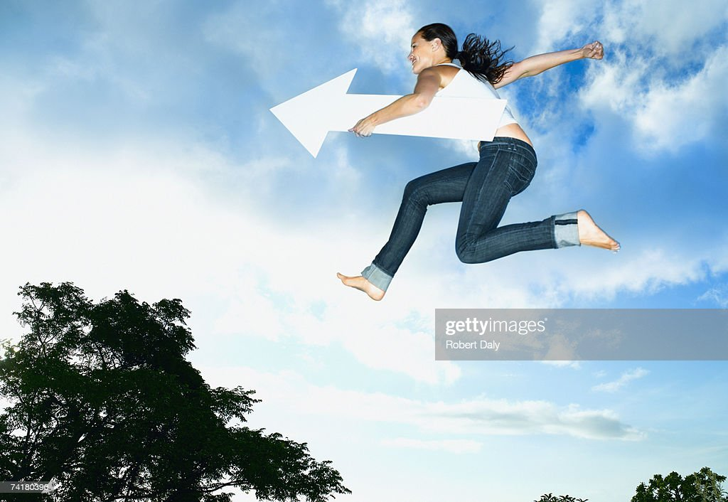 Woman with blank arrow leaping outdoors : Stock Photo