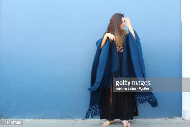 woman with blanket standing against blue wall - shawl stock pictures, royalty-free photos & images