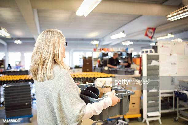 Woman with blond hair carrying crate at workshop